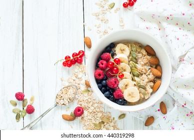 Healthy breakfast. Oatmeal porridge, banana, raspberries, blueberries, red currants, pumpkin  seeds and almonds in a  bowl on white background.
