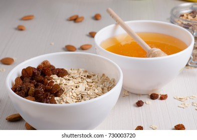 Healthy Breakfast. Oatmeal with raisins in white bowl. Almonds, honey on white  table background. Side view