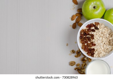 Healthy Breakfast. Oatmeal with raisins and yogurt. Milk in a glass. Fruit, nuts on a white table. Space for text.  Flat top view