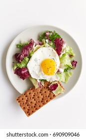 Healthy breakfast on plate consisting of fried egg, red and green lettuce and crispy bread