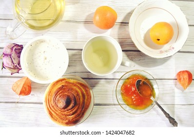 Healthy breakfast on the table with green tea cup,   glass teapot, fresh apricots, apricot jam,  twist of bread, skyr. Healthy life style. Food still life.