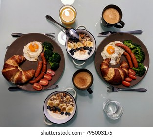 Healthy breakfast on the table. Breakfast for two. Breakfast table with yogurt, cereal and fresh fruit, eggs, croissants and broccoli, coffee and orange juice overhead shot