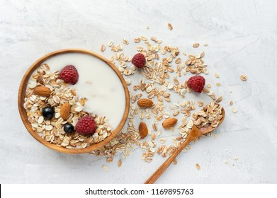 Healthy breakfast on white concrete background. Bowl of muesli with natural yogurt, almonds and fresh raspberries. Top view.