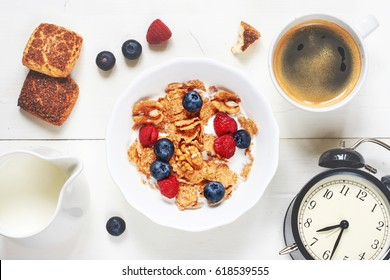 Healthy breakfast on white table. Top view of bowl of cornflakes with berries and nut, black coffee, milk, cinnamon cookie and alarm clock.