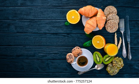 A healthy breakfast. Orange juice, kiwi, croissants, cookies, coffee, on a wooden surface. Top view. Free space for text.