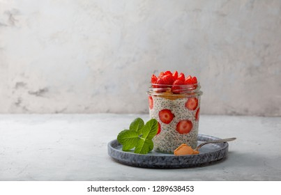 healthy breakfast. overnight oatmeal with strawberries, chia seeds in a glass jar on a gray background