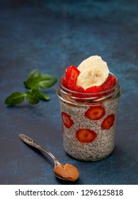 healthy breakfast. overnight oatmeal with strawberries, chia seeds in a glass jar on a blue background