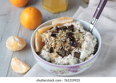 Healthy breakfast with overnight oats (Bircher muesli) topped with dried fruits and seeds.