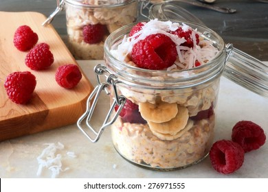 Healthy breakfast overnight oats with fresh raspberries and shredded coconut in a glass jar