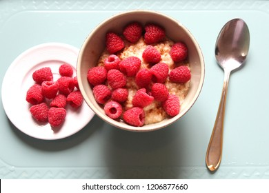 Healthy breakfast: Porridge with raspberries and cinnamon on a turquoise tray, close up
