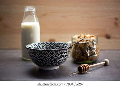 Healthy breakfast - prepared glass of milk, bowl with spoon, honey taker and glas jar of homemade granola with nuts and oats.