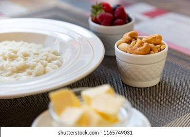 Healthy breakfast. Rice porridge bowl with berries and nuts on the table, hot and healthy breakfast food, side view