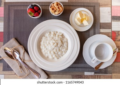Healthy breakfast. Rice porridge bowl with berries and nuts on the table, hot and healthy breakfast food, top view