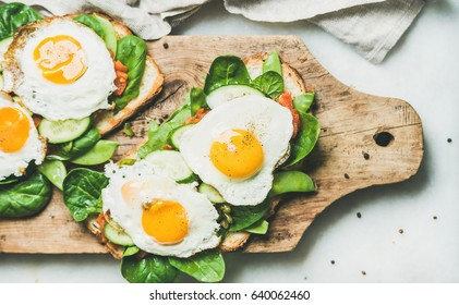 Healthy breakfast sandwiches. Bread toasts with fried eggs and fresh vegetables on rustic wooden board over grey marble background, top view. Clean eating, healthy, diet, weight loss food concept