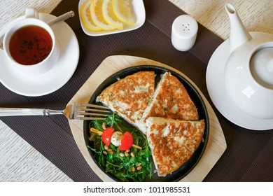 A healthy breakfast, scrambled eggs, tea, cheese, butter, fresh herbs. Top view, close-up. Healthy food.