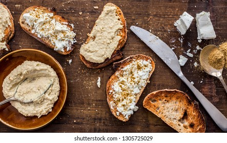 Healthy breakfast with seeded bread slices and white feta cheese and houmous on top on brown rustic wooden background