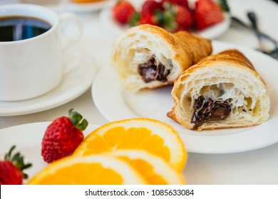 Healthy breakfast served with black coffee, croissant, orange juice and fruits