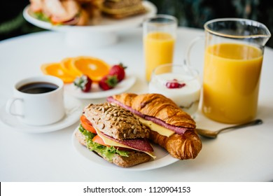 Healthy breakfast served with black coffee, sandwiches, muesli and orange juice