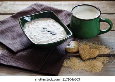 Healthy breakfast . Sesame dry cookies in the shape of heart, porridge of amaranth and yogurt on old wooden table