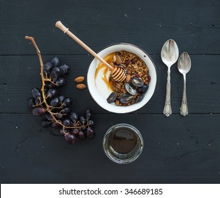 Healthy breakfast set. Bowl of oat granola with yogurt, fresh grapes, almond and  honey over black wooden backdrop. Top view