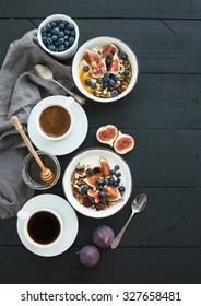 Healthy breakfast set. Bowls of oat granola with yogurt, fresh blueberries and figs, coffee, honey, over black wooden backdrop. Top view, copy space