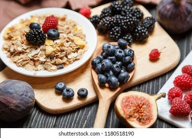 Healthy breakfast set. Muesli and berries on dark rustic background