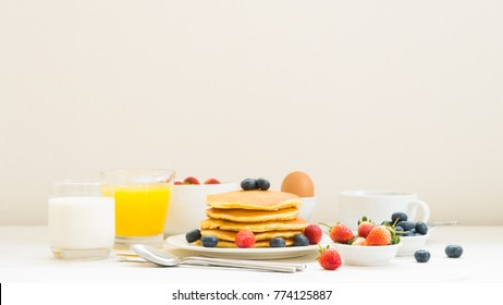 Healthy Breakfast set with Pancake and Granola with blueberry and strawberry and black coffee , Milk and Orange juice on white stone table background
