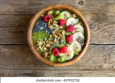 Healthy breakfast smoothie bowl topped with fruits, nuts, berries and seeds over rustic wooden background