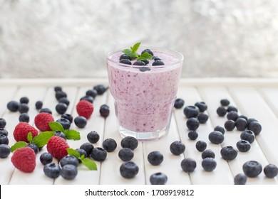 Healthy breakfast of smoothie, dessert, yogurt or milkshake with fresh berries on whtite wooden table