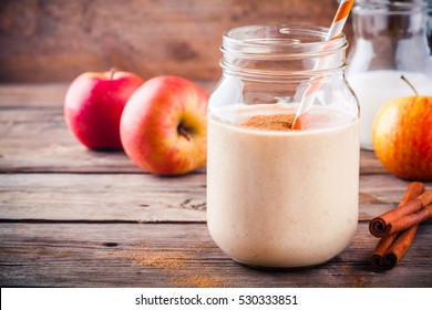 Healthy breakfast: smoothies with red apple and cinnamon in a glass mason jar on a wooden background