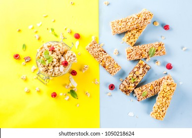 Healthy breakfast and snack concept, homemade granola with fresh raspberries and nuts in jar and granola bars, on bright yellow and blue background copy space seamless pattern