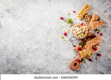 Healthy breakfast and snack concept, homemade granola with fresh raspberries in jar and nuts and granola bars, on grey stone stone background copy space top view