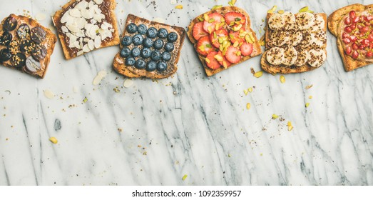 Healthy breakfast or snack. Flat-lay of vegan whole grain toasts with fruit, seeds, nuts and peanut butter over marble background