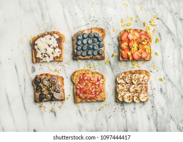 Healthy breakfast or snack. Flat-lay of vegan whole grain toasts with fruit, seeds, nuts and peanut butter over marble background, top view. Clean eating, vegetarian, dieting food concept