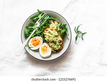 Healthy breakfast or snack - mashed avocado sandwich and boiled egg on a light background, top view