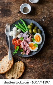 Healthy breakfast or snack - plate of canned tuna, green beans, mozzarella cheese, tomatoes, boiled egg, olives, grilled bread a wooden dark background, top view