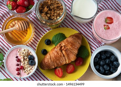 healthy breakfast of strawberry smoothie, fresh strawberries and croissants with honey