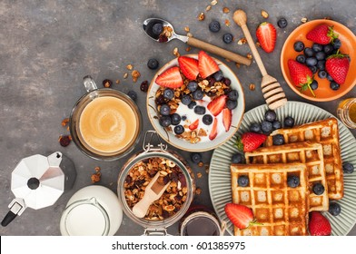 Healthy breakfast table with cereal granola, milk, fresh berries, coffee and waffles, top view