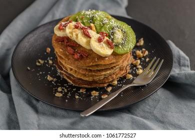 Healthy breakfast table,  homemade pancakes with kiwi, banana, goji and walnuts.