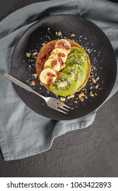 Healthy breakfast table,  homemade pancakes with kiwi, banana, goji and walnuts.