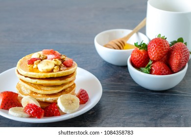Healthy breakfast table withhomemade pancakes, exotic fruits and coffee