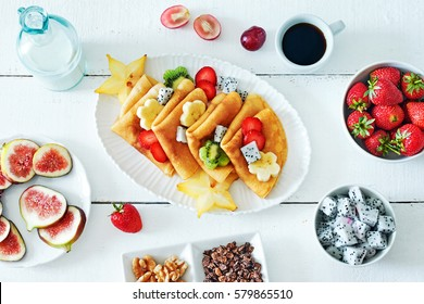 Healthy breakfast with thin pancakes, exotic fruits (starfruit, pitaya, banana, kiwi), strawberry, figs, granola, coffee and milk on a white table.
