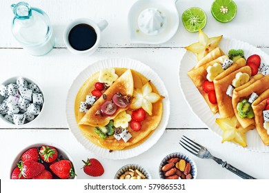 Healthy breakfast with thin pancakes, exotic fruits (starfruit, pitaya, banana, kiwi), strawberry, figs, granola, coffee and milk on a white table.