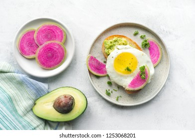 Healthy breakfast. Toast made from sliced watermelon radish (chinese daikon), avocado and roasted egg. Top view.