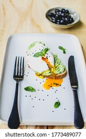 Healthy breakfast, Toasted bread with avocado and benedict poached egg and fresh basil