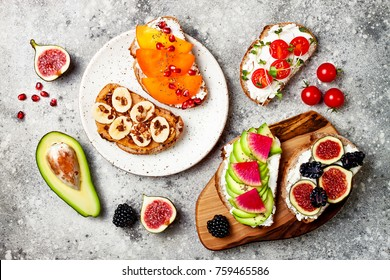 Healthy breakfast toasts with avocado, tomato, peanut butter, banana, chocolate granola, cream cheese, figs, blackberry, persimmon, pomegranate, chia seeds. Top view, overhead
