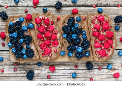 Healthy breakfast toasts for kids with peanut butter fresh berries and pomegranate seeds on rustic wooden table. top view