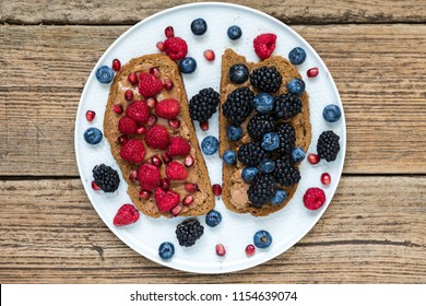 Healthy breakfast toasts for kids with peanut butter fresh berries and pomegranate seeds in a plate on rustic wooden table. top view