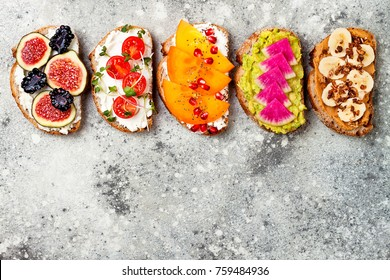 Healthy breakfast toasts with peanut butter, banana, chocolate granola, avocado, watermelon radish, persimmon, pomegranate, chia seeds, tomato, figs, blackberry. Copy space