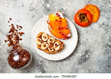 Healthy breakfast toasts with peanut butter, banana, chocolate granola, cream cheese, persimmon, pomegranate, chia seeds. Top view, overhead, copy space